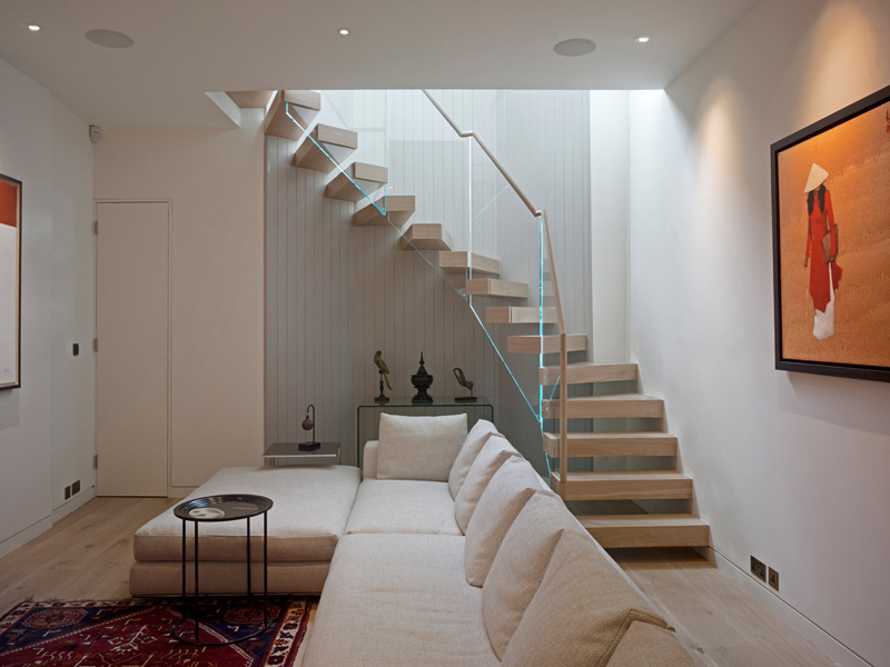 Ladbroke Road, basement tv / cinema room with timber and glass stair with artwork